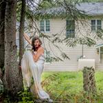 Artist Lara Kramer standing by tree in front of former Pelican Lake Indian Residential School